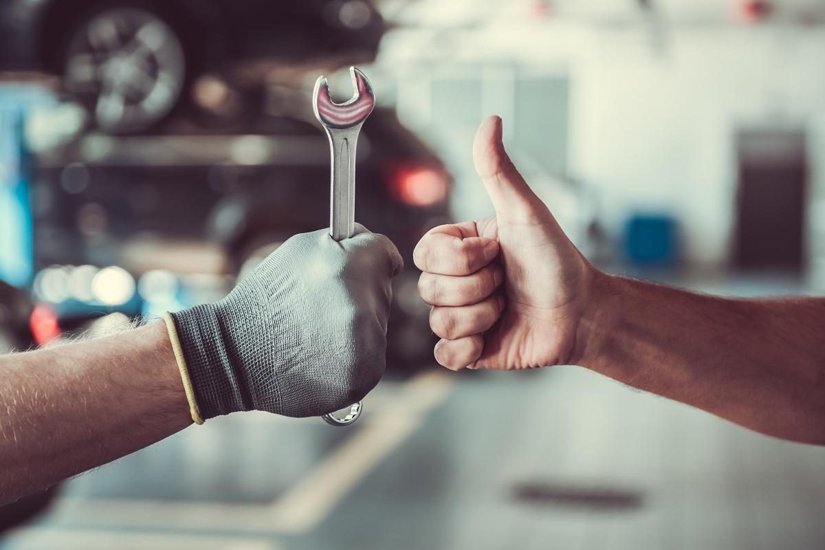 Car mechanic and customer fist bump