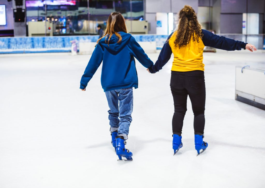 Two girls holding hands trying not ot fall on the ice