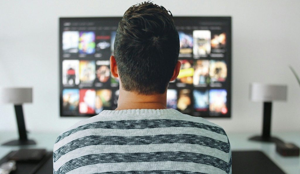 man searching for a movie to watch
